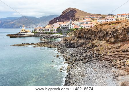 Coast in Madeira with sea stony beach mountains and village with houses