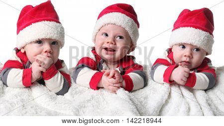 Three Christmas baby boys wearing Santa hats.