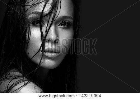 Beautiful girl with a bright make-up and wet hair and skin. Beauty face. Black and white photo. Picture taken in the studio on a black background.