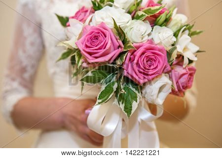The bride's bouquet in her hands. Beautiful flowers roses bouquet - wedding accessory. Flowers for the holiday.