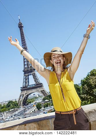 Happy Young Woman Rejoicing Against Eiffel Tower In Paris