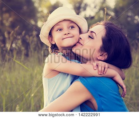 Beautiful Happy Mother Hugging And Kissing Her Grimacing Fun Daughter On Summer Bright Background. C