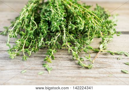 Sprigs of thyme on an old wooden background.
