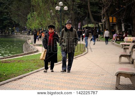Hanoi, Vietnam - 10 March,2012: Old couple walking together around Hoan Kiem lake