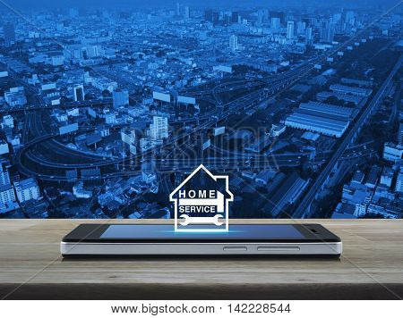 Hammer and wrench with house icon on modern smart phone screen on wooden table over city tower street and expressway Home service concept