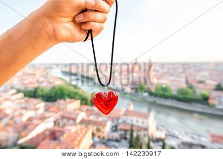 Holding decoration in the form of heart on the italian town Verona background. Verona is famous city of love in the north of Italy.