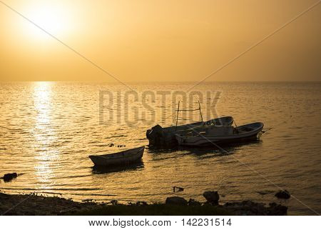 CAMPECHE, MEXICO - JULY 8, 2016: Three Mexican panga fishing boats sit quietly moored near shore in the calm water of the Gulf of Mexico backlit by a golden setting sun.