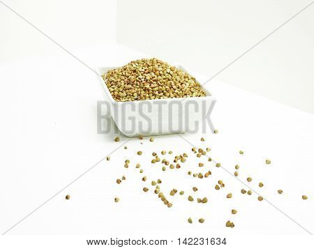 Buckwheat in white plate isolated on white background.