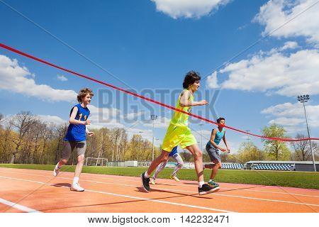 Side view portrait of teenage boy, happy winner, crossing finish line on the racetrack