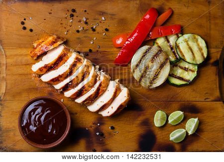 Barbecue grilled chicken and vegetables - zucchini, bell pepper, onion and barbecue sauce on wooden cutting board. Top view