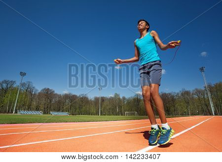 Bottom view of smiling African teenage athlete skipping the rope on the stadium in the park