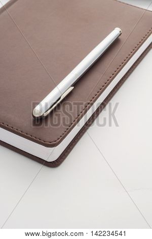 Metal Handle Lying On A Leather-bound Brown Diary Which Belongs To Businessman. Veritkalny Frame.