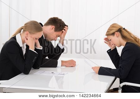 Three Unhappy Young Businesspeople Sitting In Office