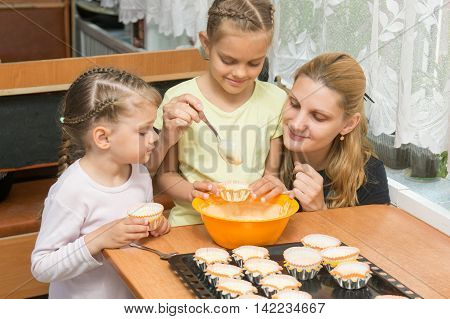 The Elder Daughter Pours Batter For Cakes In Tins, Under The Care Of My Mother And Younger Sister