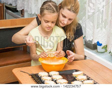 Mom And Daughter Seven Years Pour The Batter Into The Mold For Baking Muffins