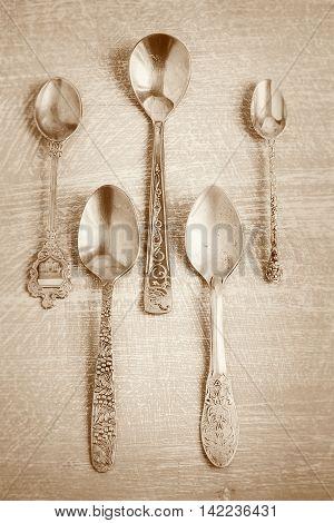 Old teaspoons on vintage background. Monochromatic photo in retro Style
