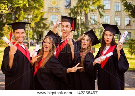 Successful Excited Five Graduates In Robes Standing In Row And Showing Certificate