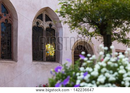 Sunlight shines through the stained glass windows of a church in Mittelbergheim Alsace