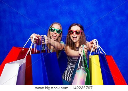 Glad Smiling Girls In Spectacles Showing Their Purchases