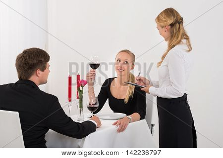 Waitress Taking An Order From A Couple Drinking Glass Of Red Wine