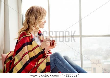 Portrait of woman basking with plaid and tea looking in window