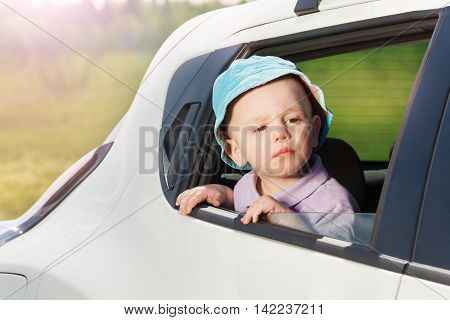 Cute little boy in bucket hat, peering out the open car window observing nature on sunny day