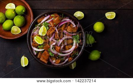 Seafood. Salad ceviche of edible seaweed cochayuyo whith onion cilantro and lemon in clay bowl on black background. Traditional food of indian mapuche. Top view