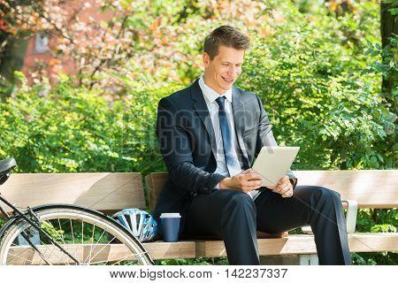 Smiling Male Businessman Sitting On Bench Using Digital Tablet At Park