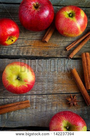 Apples cinnamon and star anise on old wooden background.