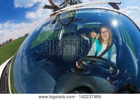 Happy female driver travelling by car with two kid boys on sunny day, view through a windscreen, shot with wide angle lens