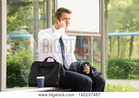Young Businessman Talking On Mobile Phone While Waiting At Bus Stop