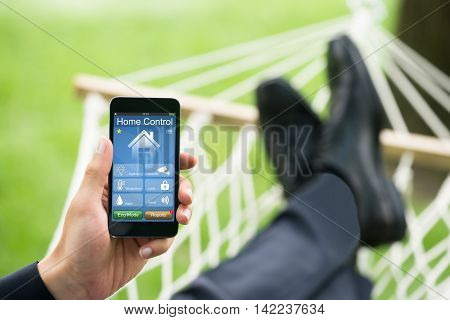 Close-up Of Man In Hammock With Mobile Phone Showing Home Control System