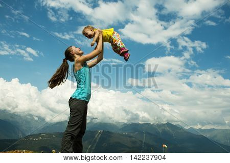 Mother throws up her baby in the sky in nature. hot summer day in the mountains