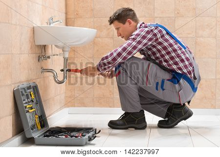 Young Male Plumber Fitting Sink With Wrench In Bathroom