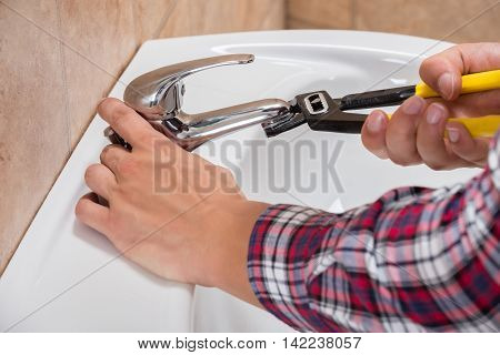 Close-up Of Plumber Installing Faucet Of Sink With Wrench