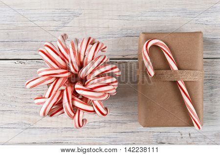A jar full of candy canes and a plain brown paper wrapped Christmas present on a rustic white wood table.