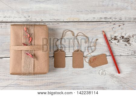 Top view of a Christmas present wrapped with brown paper, burlap ribbon and flowers next to gift tags and a red pencil.