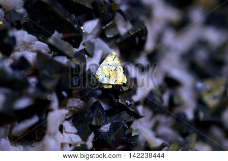 macro shot of raw pyrit crystal trapped in dark material