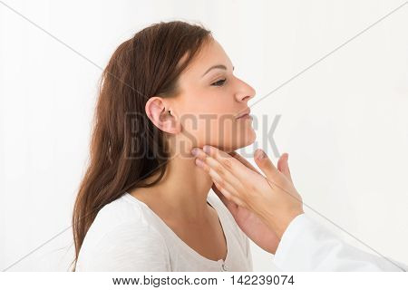 Close-up Of A Doctor's Hand Touching The Throat Of A Female Patient In The Clinic