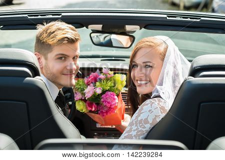 Young Smiling Just Married Couple With Bouquet In The Car