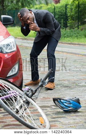 Shocked Male Driver With Hands On Head Looking At Bicycle After Collision On Street