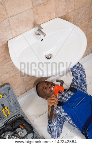 Happy Young African Male Plumber Fixing Sink In Bathroom