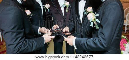 Group of groomsman standing in circle and using phones.
