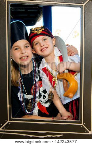 Two siblings pose for a photo while dressed in pirate clothes. They are framed by a hole they are looking through. The older sister has colorful braces and both are smiling.