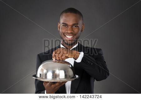 Portrait Of Happy Waiter Serving Meal In Cloche