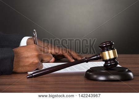 Close-up Of A Judge Writing On Paper With Gavel At Desk