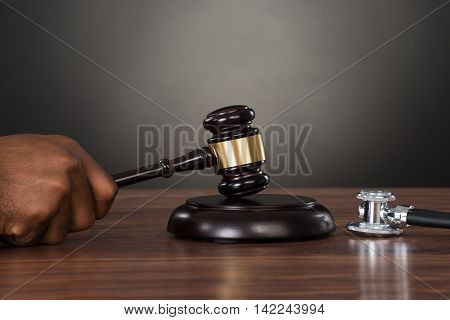 Close-up Of A Judge Hands Striking Gavel With Stethoscope At Desk