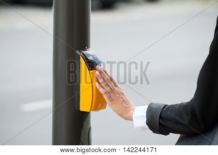 Close-up Of Businesswoman Hand Pressing Yellow Crosswalk Button
