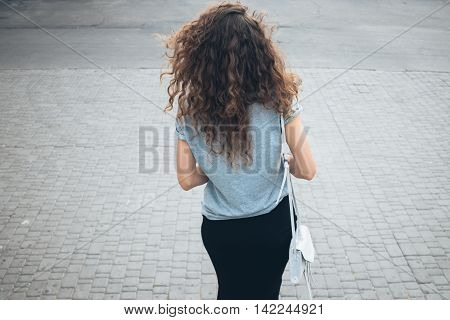 Slender young girl with magnificent curly hair in a skirt and with handbag walking on a city in the summer the view from the back