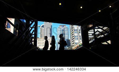 Three millennials walking past a dark stairway in Seattle